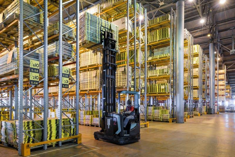 Работник нагружает товары в большом складе стоковое фото rf