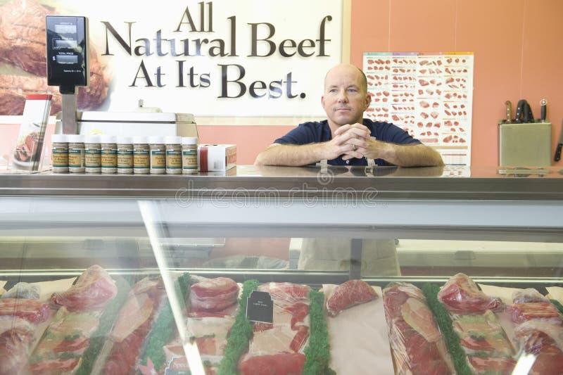Работник на счетчике мяса в супермаркете стоковые фото