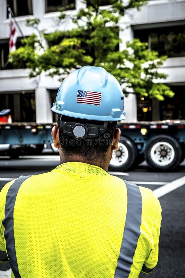 Работник нося голубой шлем безопасности с флагом США стоковые фотографии rf