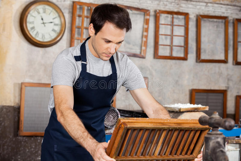 Работник окуная прессформу в пульпе и воде стоковое фото