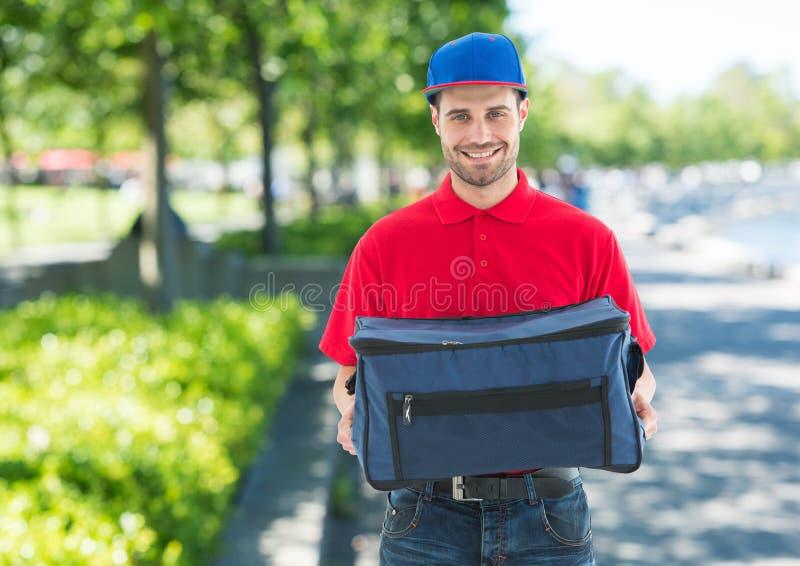 Работник доставляющее покупки на дом пиццы с голубой шляпой и поставка кладут в мешки в парке стоковые изображения rf