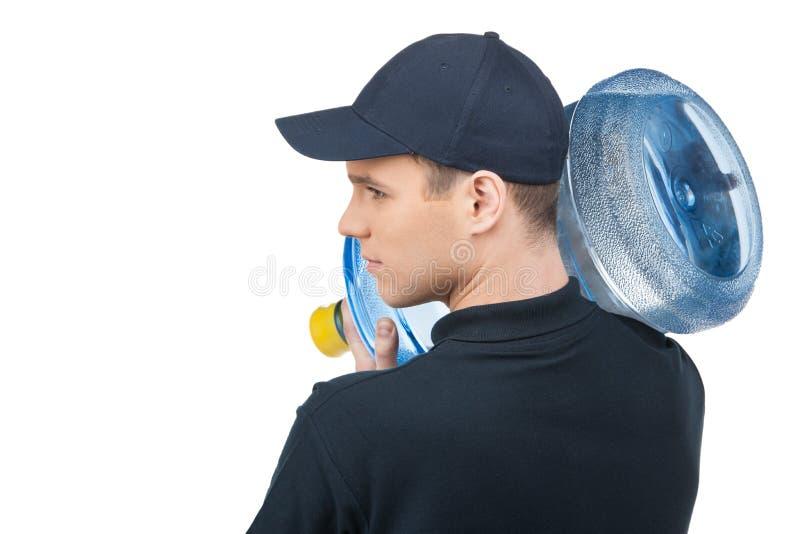 Работник доставляющее покупки на дом с кувшином воды. Вид сзади уверенно молодого deliv стоковые изображения rf