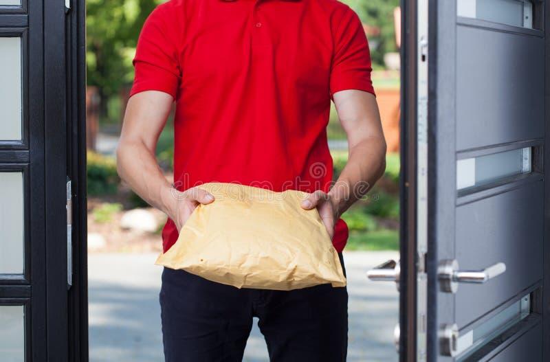 Работник доставляющий покупки на дом давая пакет стоковое фото