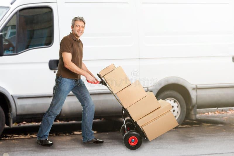 Работник доставляющий покупки на дом нажимая пакеты на Handtruck стоковые фотографии rf