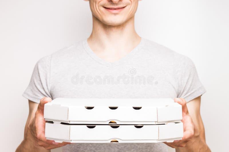 Работник доставляющий покупки на дом пиццы держит 2 коробки стоковое изображение