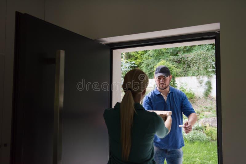 Работник доставляющий покупки на дом пиццы стоковые изображения