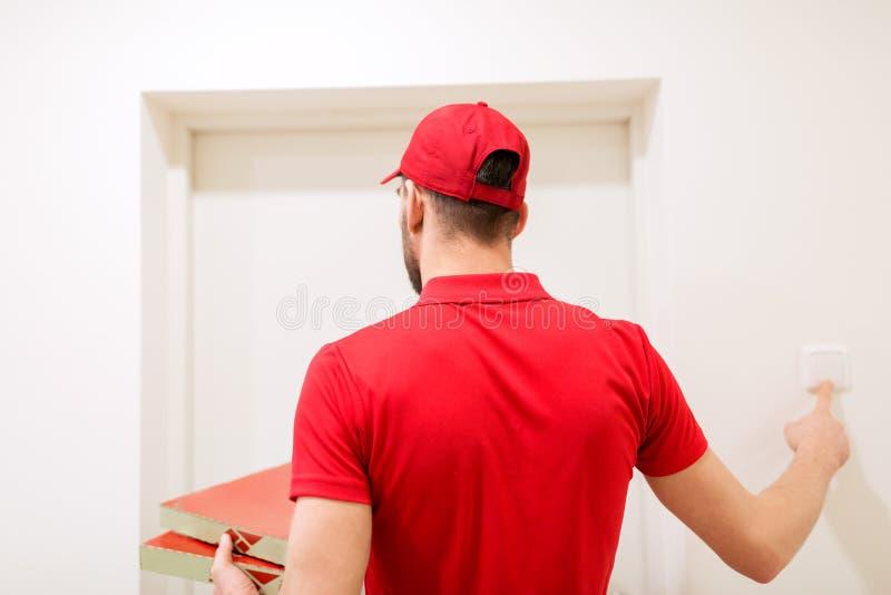 Работник доставляющий покупки на дом при коробки пиццы звеня дверной звонок стоковое фото rf
