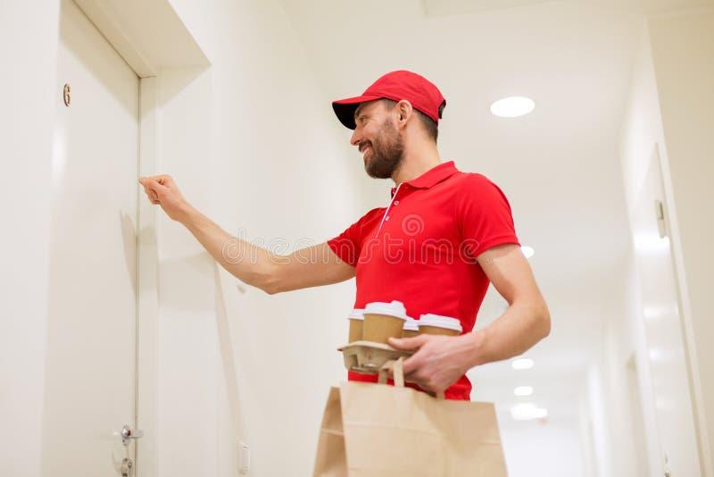 Работник доставляющий покупки на дом при кофе и еда стучая на двери стоковые изображения rf