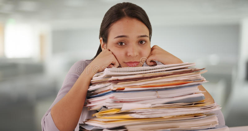 Работник офиса латиноамериканца усиленный от слишком много обработки документов стоковые фото