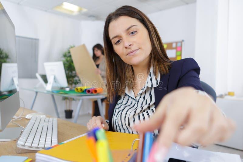 Работник офиса женщины достигая что-то стоковые изображения rf