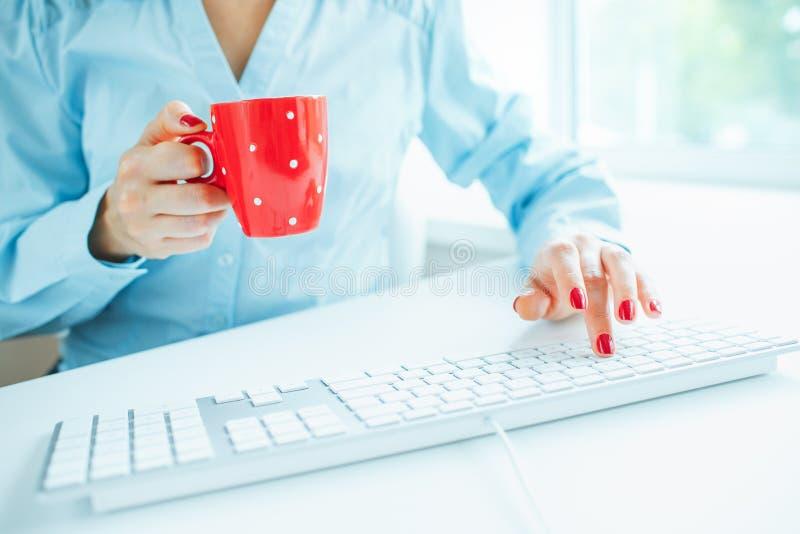 Работник офиса женщины печатая на клавиатуре и выпивая кофе стоковые фото