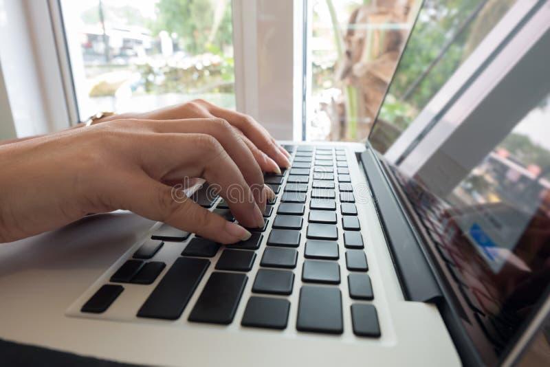 Работник офиса женщины печатая на клавиатуре компьтер-книжки стоковая фотография