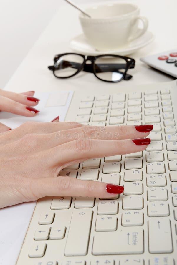 Работник офиса женщины печатая на клавиатуре стоковое фото rf