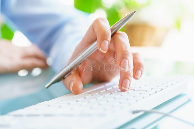 Работник офиса женщины с ручкой в руке печатая на клавиатуре стоковые фотографии rf