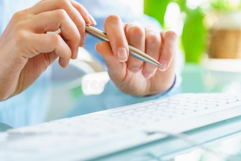 Работник офиса женщины с ручкой в руке печатая на клавиатуре стоковая фотография