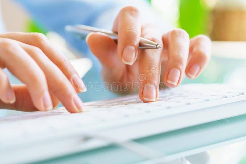 Работник офиса женщины с ручкой в руке печатая на клавиатуре стоковое изображение rf