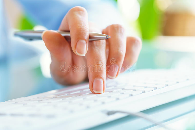 Работник офиса женщины с ручкой в руке печатая на клавиатуре стоковые изображения rf