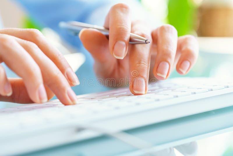 Работник офиса женщины с ручкой в руке печатая на клавиатуре стоковое изображение