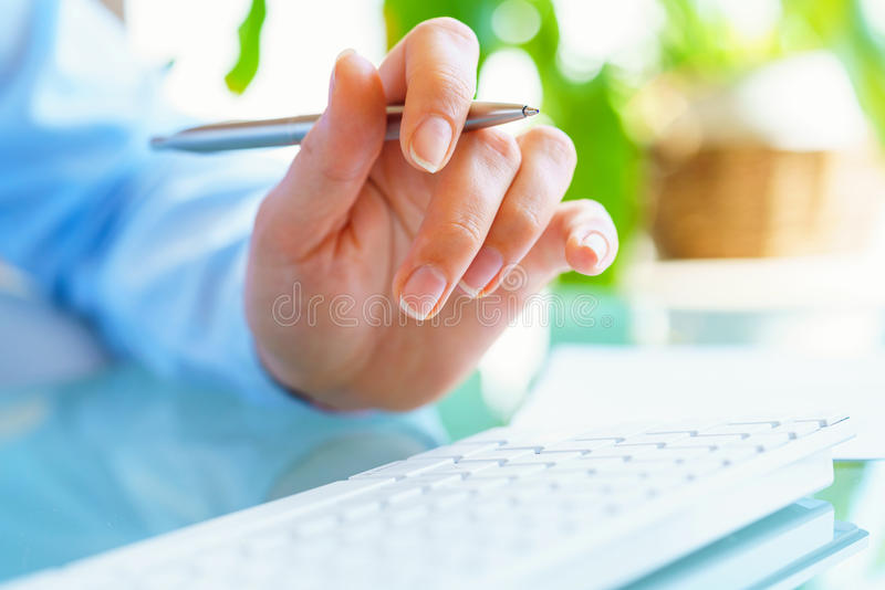 Работник офиса женщины с ручкой в руке печатая на клавиатуре стоковое фото rf