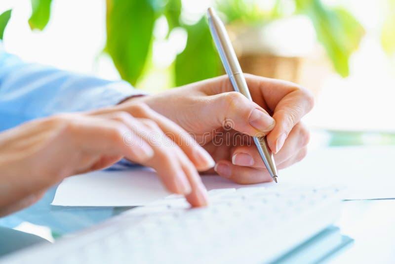 Работник офиса женщины с ручкой в руке печатая на клавиатуре стоковые фото