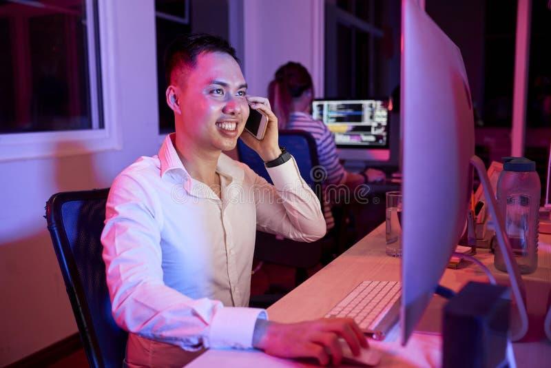 Работник офиса имеет телефонный звонок на офисе стоковая фотография
