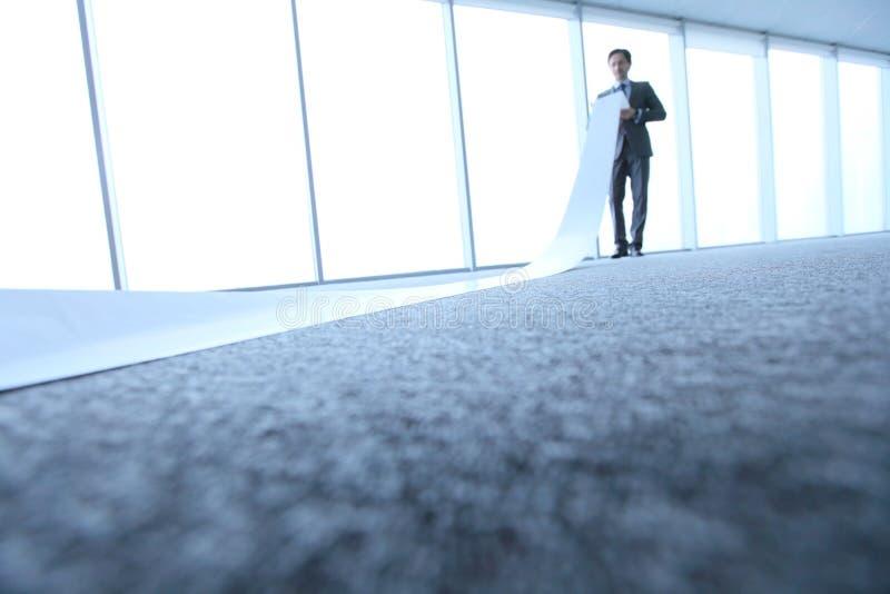 Работник офиса разворачивая длинный лист стоковое изображение