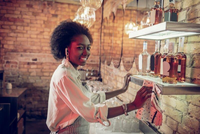работник паба Молод-взрослого Афро-американский tidying вверх по полкам кухни с полотенцем стоковое изображение