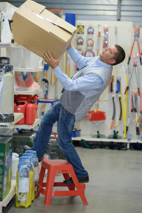 Работник падая лестница в складе стоковые фото