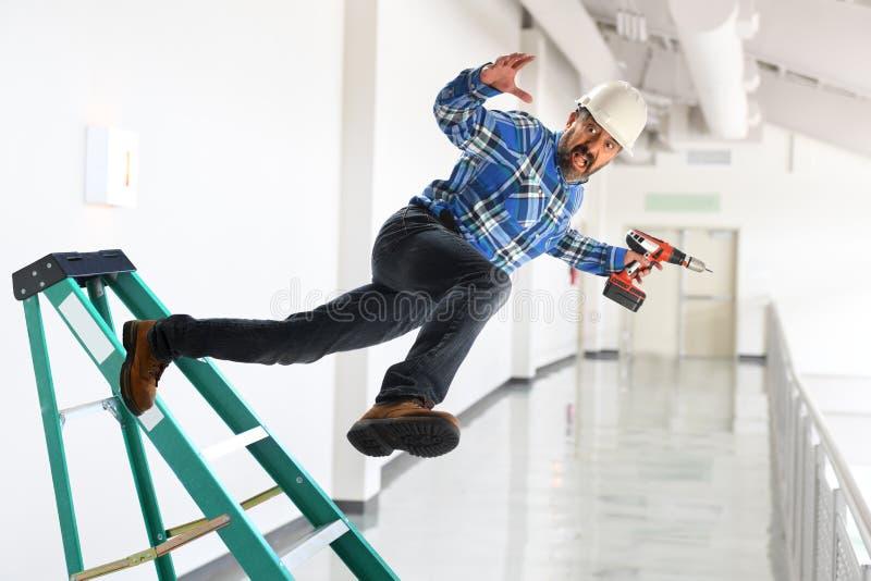 Работник падая лестница стоковые изображения