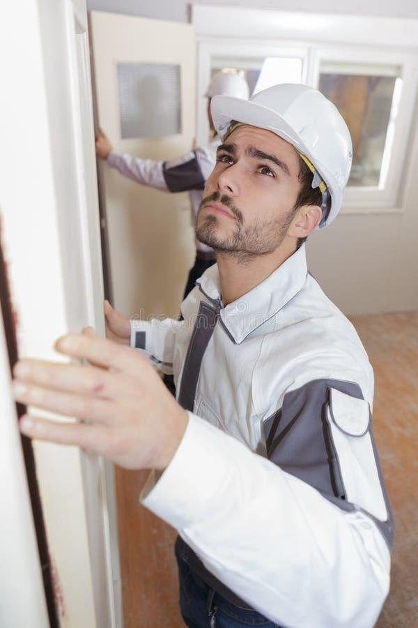 Работник плотника на установке двери стоковые фотографии rf