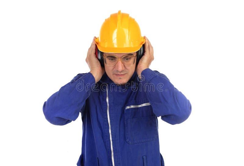 Работник покрывая его уши с желтым шлемом стоковое изображение rf