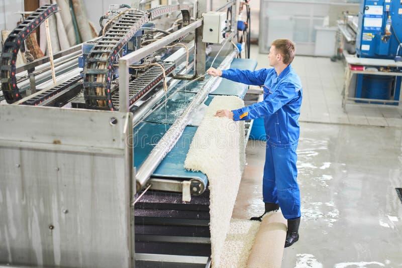 Работник прачечной в процессе работы на автоматической машине для стирки ковра стоковое изображение rf