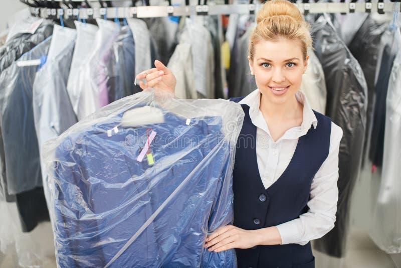 Работник прачечной девушки держа вешалку упаковал с чистыми одеждами стоковые фото