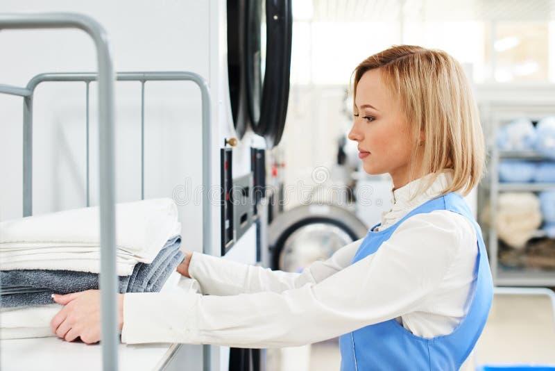 Работник прачечной девушки кладет чистые одежды на полку стоковая фотография rf