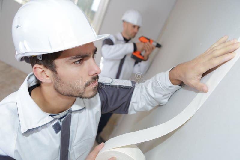 Работник прикладывая ленту для маскировки к стене стоковое фото rf