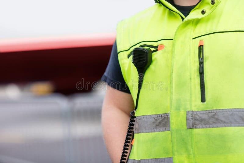 Работник при микрофон прикрепленный на отражательной куртке на авиапорте стоковое изображение rf