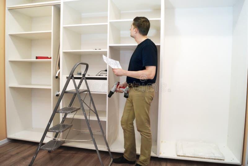 Работник при отвертка проверяя новый шкаф стоковые фото