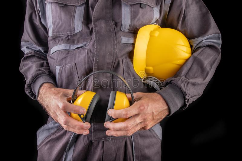 Работник продукции в workwear со шлемом и протекторы слуха в руке Особенный workwear для работников стоковые фотографии rf