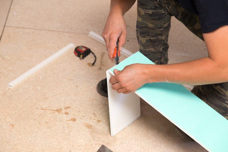 Работник работает с пластмассой для окон в доме стоковая фотография