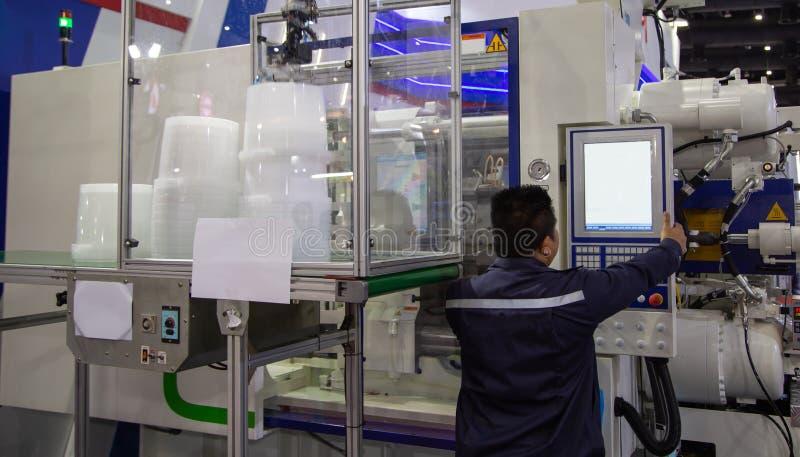 Работник работая пластиковую машину инжекционного метода литья стоковое изображение rf