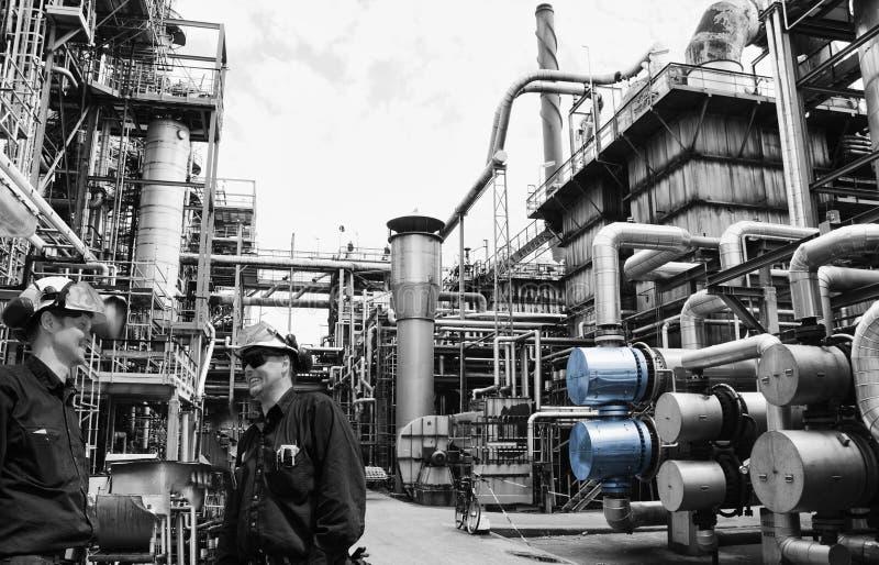 Работник рафинадного завода внутри гиганта прокладывает трубопровод конструкции стоковая фотография rf