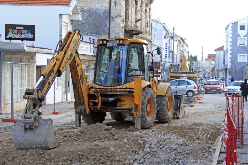 Работник ремонта дороги используя экскаватор внешний в Мостаре стоковое фото