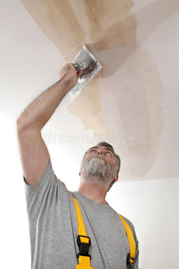 Работник ремонтируя гипсолит на потолке стоковое фото