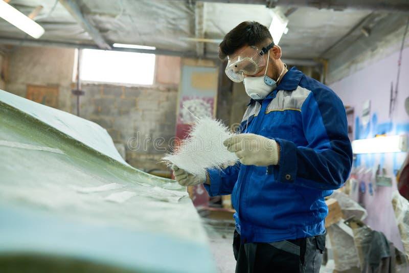 Работник ремонтируя шлюпку в мастерской стоковые фотографии rf