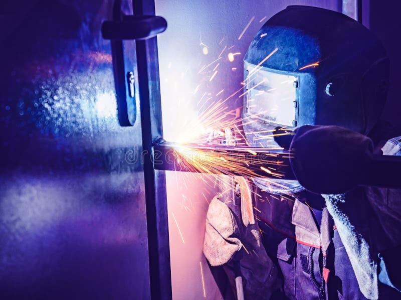 Работник сварщика выполняет заварку скачки Сварщик работника выполняет процесс электродуговой сварки структур металла Искры летая стоковые изображения