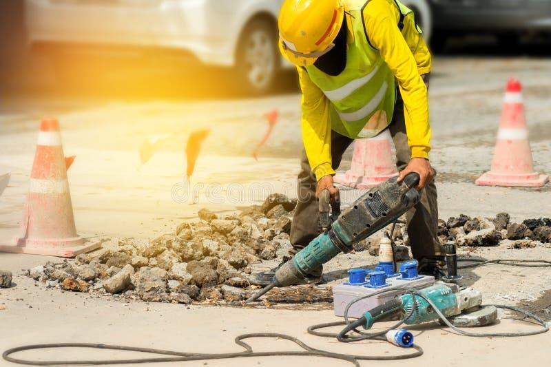 Работник сверля конкретную подъездную дорогу с jackhammer Ремонтировать человека стоковые фото