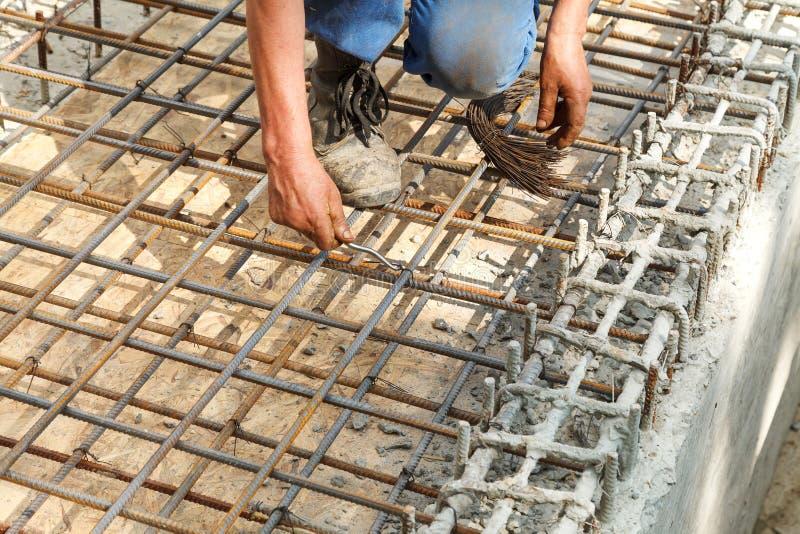 Работник связывает стальные усиливая бары с проводом стоковое фото