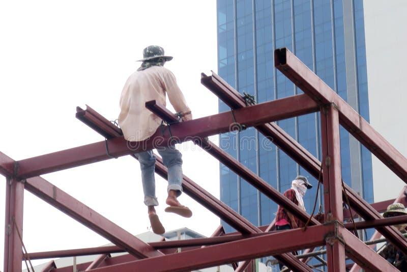 Работник сидя на высоком прогоне стоковое фото