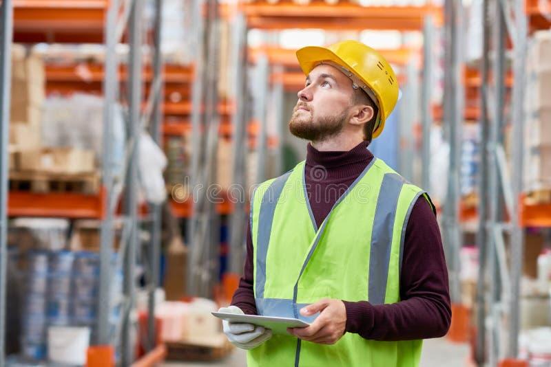Работник склада используя цифровую таблетку стоковая фотография