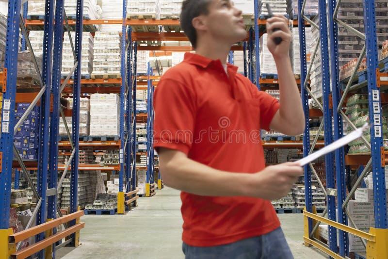 Работник склада используя звуковое кино Walkie стоковые изображения
